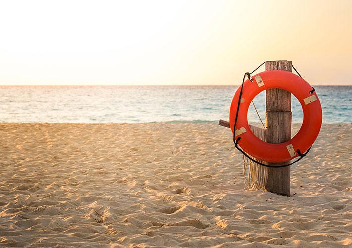 Hilfe bei Schlaganfall Bild am Strand mit Rettungsring am Pfeiler im Sand steckend hängend